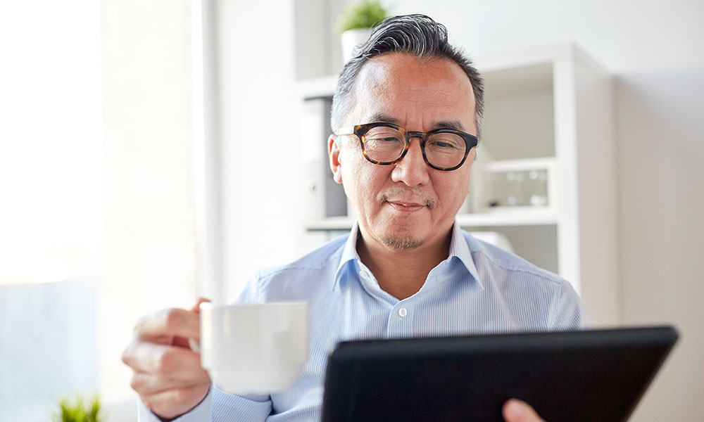 An Asian man in his mid-50s drinks a cup of coffee and works from his iPad; remote-based ambassadors