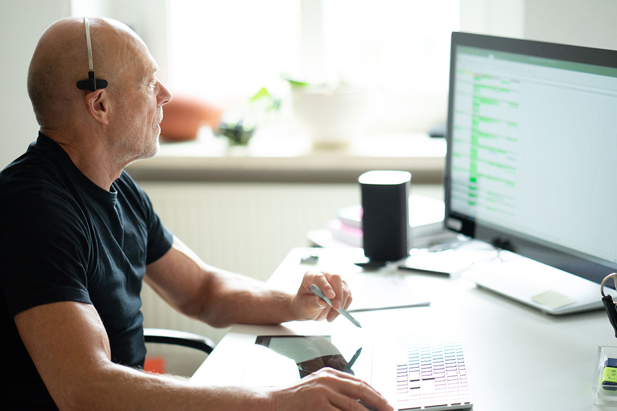 An older bald man in a black shirt wears a headset while working on the desktop in his home office; customer service experience