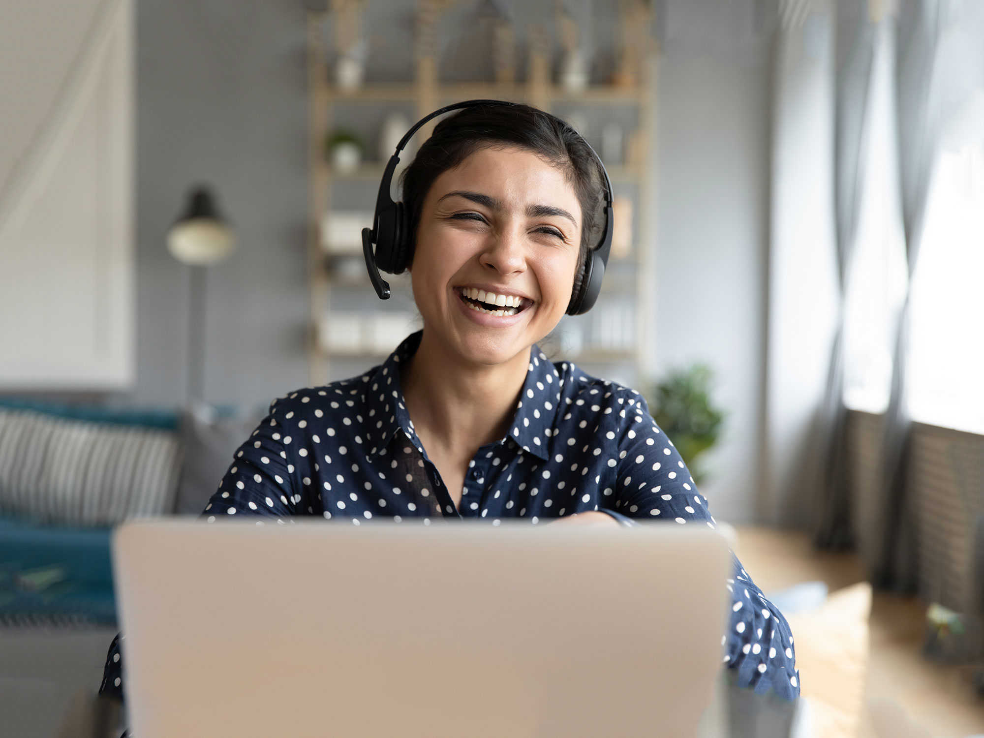 A woman in her mid-20s wearing a headset laughs; customer experience outsourcing