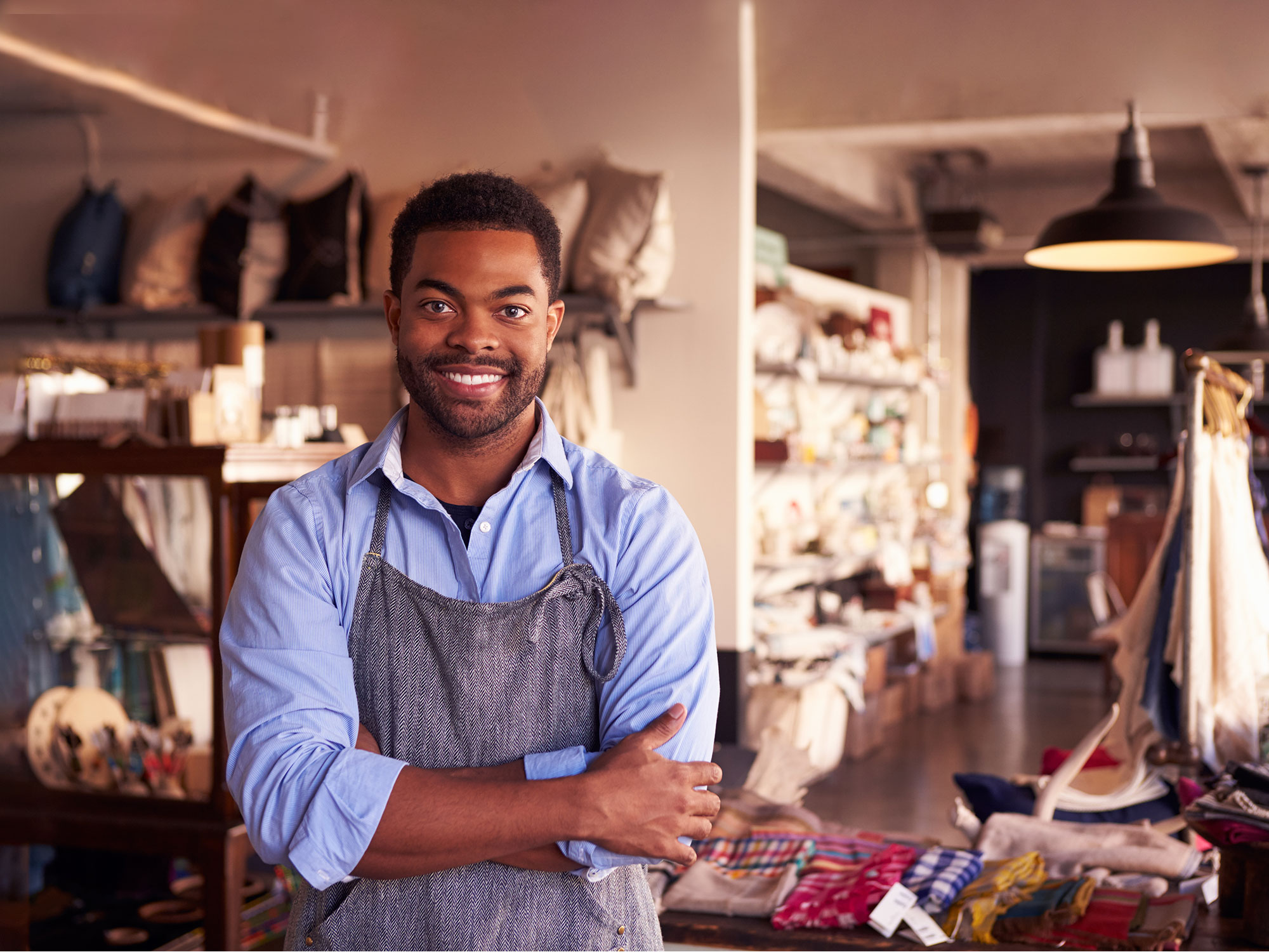 An African American man wearing an apron and blue shirt smiles; customer experience solutions