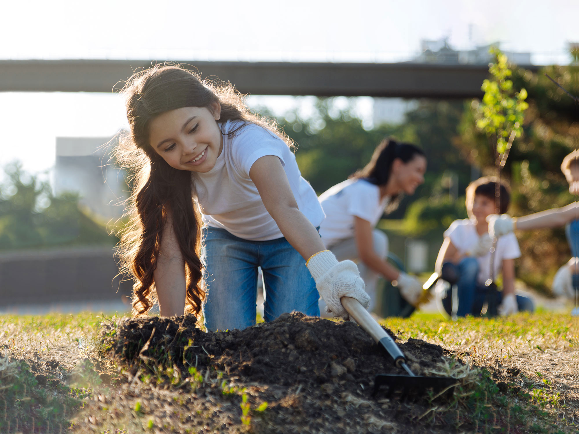 A young girl smiles while working in a community garden; demonstrates corporate social responsibility