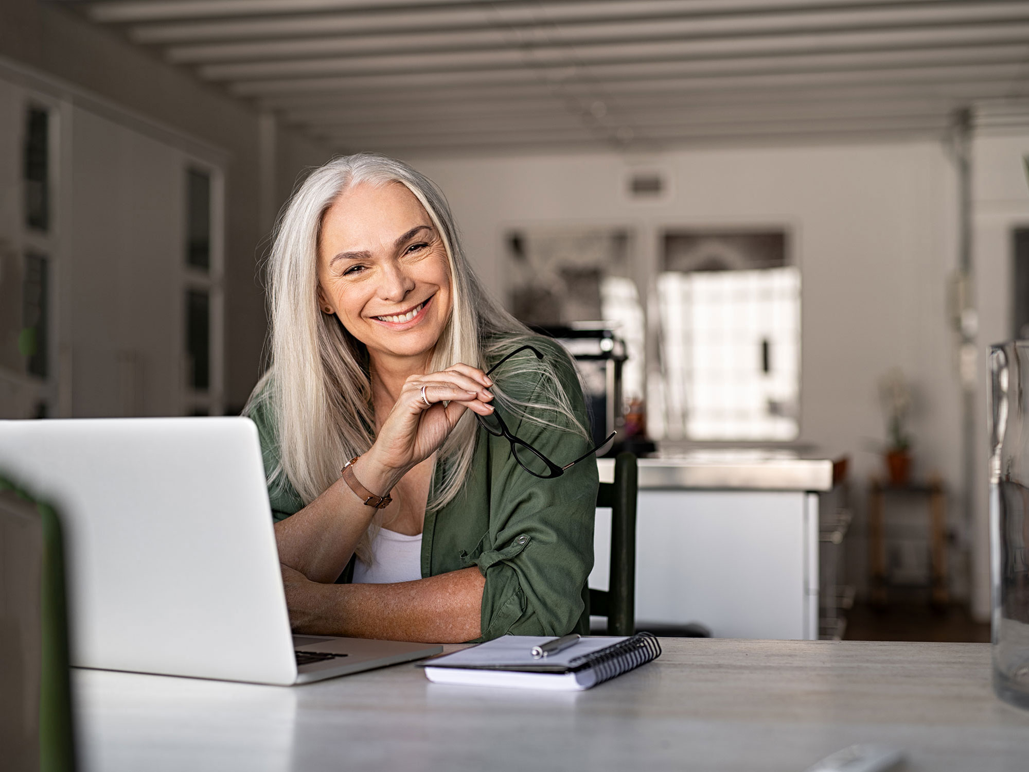 A woman in her 50s with long white hair sits at her laptop and smiles into the camera; customer experience provider